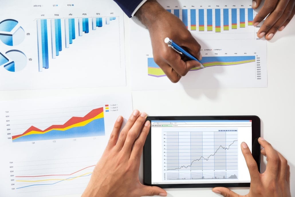 High Angle View Of Two Businesspeople Analyzing Graph By Using Digital Tablet